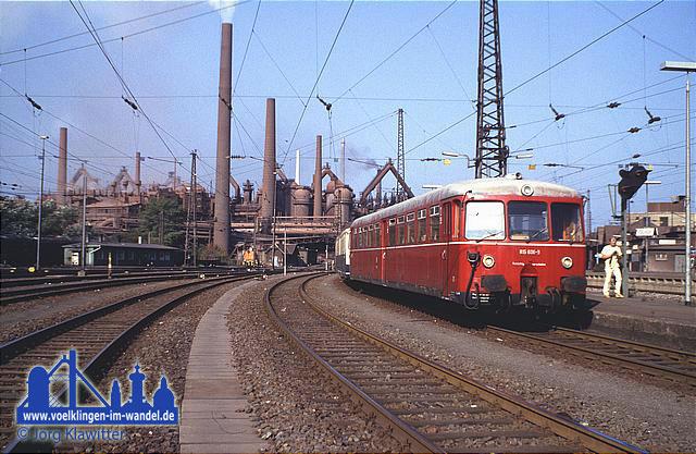 Am 29. September 1985 fuhr ein Sonderzug aus 515/815 auf der Köllertalbahn Völklingen- Lebach. Anlass war die Einstellung des Personenverkehrs auf der Gesamtstrecke. Hier steht der Sonderzug mit 2x 515 und 2x 815 des Bw Worms abfahrbereit auf Gleis 5 vor der imposanten Kulisse der ebenfalls um diese Zeit stillgelegten Völklinger Hütte. © Jörg Klawitter