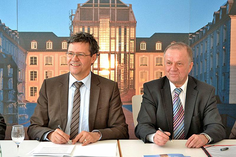 Bildunterschrift: Regionalverbandsdirektor Peter Gillo und SHG-Geschäftsführer Alfons Vogtel unterschreiben die Vereinbarung im Saarbrücker Schloss Bild: Regionalverband