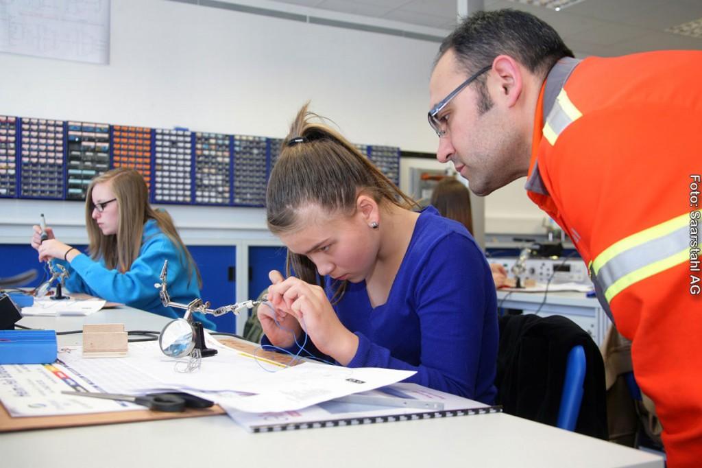 Janice Burgard (links) und Nina Meiser mit Ausbilder Recep Gülpinar hochkonzentriert bei der Arbeit in der Elektroabteilung.
