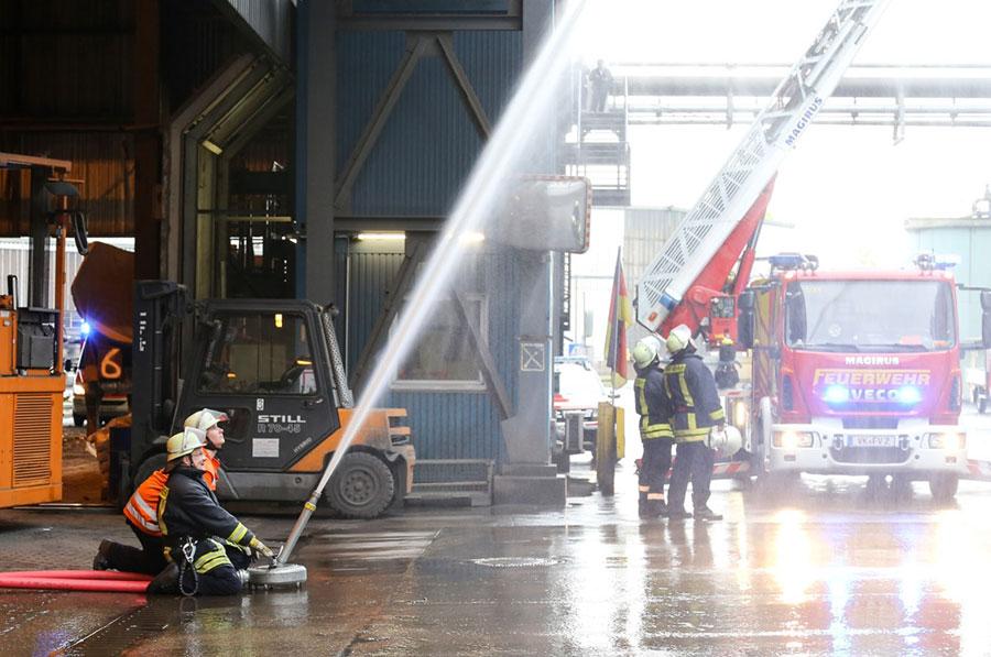 Die Werkfeuerwehr kühlt die Fassade während die Freiwellige Feuerwehr der Mittelstadt Völklingen (rechts im Bild) die Drehleiter ausfährt. (Foto: Saarstahl AG)