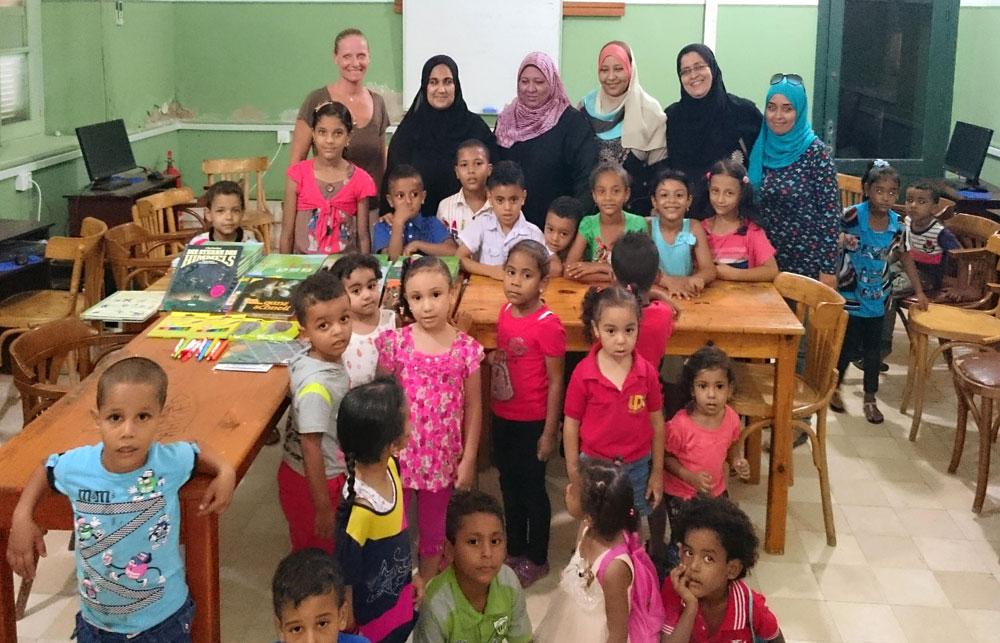 Sabine Schroeder (h.l.) hat die 30 Atlanten zusammen mit einigen Märchenbüchern und Buntstiften persönlich den Erzieherinnen und Schülerinnen und Schüler in einem Unterrichtsraum in El Quseir überbracht