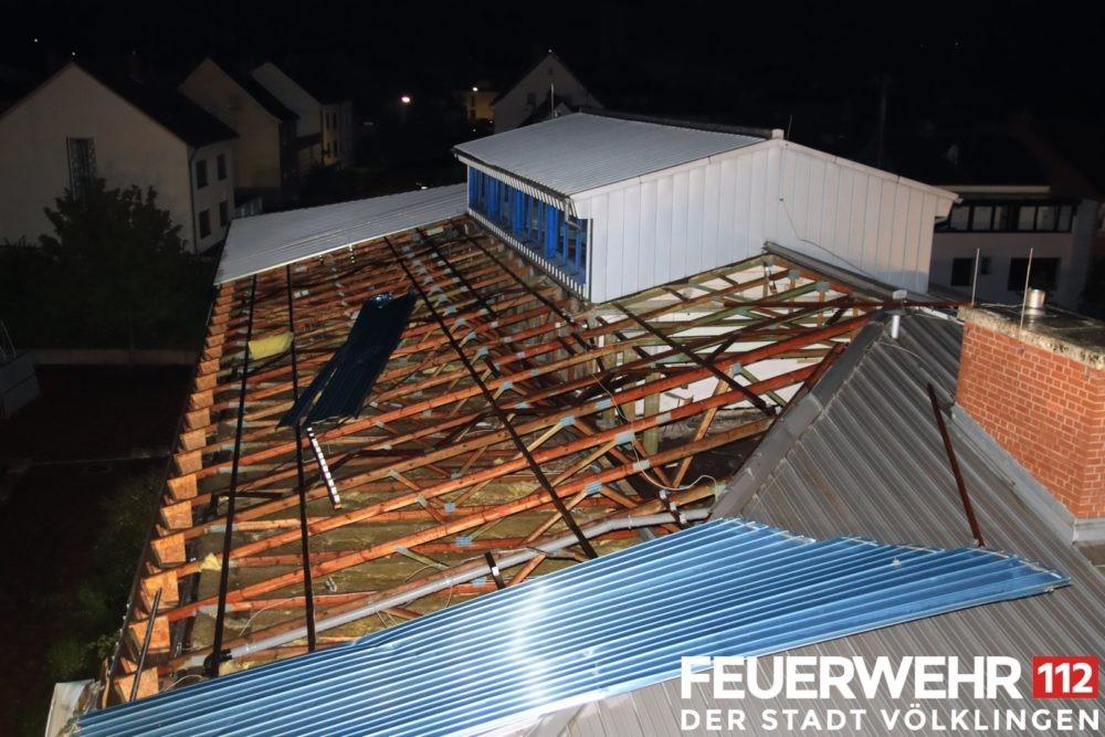 """Die Feuerwehr wurde wegen eines Sturmschadens an einem Dach in die """"Kleine Bergstraße"""" alarmiert. Dort stellte sich heraus, dass es zu einer Teilabdeckung des Daches an der dortigen Grundschule gekommen war. Die Einsatzkräfte sicherten die Einsatzstelle ab und entfernten Dachteile, die auf der Straße lagen. Ausserdem wurden die angrenzenden Wohnhäuser auf weitere Schäden und dadurch entstehende Gefahren untersucht. Durch den Bauhof wurde die gesamte Straße gesperrt. Auch musste die Stromversorgung durch die Stadtwerke Völklingen abgestellt werden, da zwei Dachständer für die Elektrozuleitung in Mitleidenschaft gezogen wurden. Wegen des Schadens wurde die Grundschule für den Schulbetrieb an diesem Tag gesperrt. (Bild und Bildunterschrift: Feuerwehr Völklingen, W. Schmidt)"""