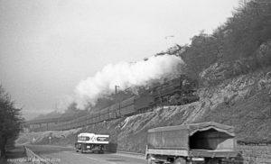 29.3.1968: Die Ehranger 44 1512 aus Richtung Trier - interessanter LKW Verkehr auf der heutigen B51 - im Hintergrund die Brücke zum Heidstocktunnel der Köllertalstrecke (Foto: Reinhard Gumbert)