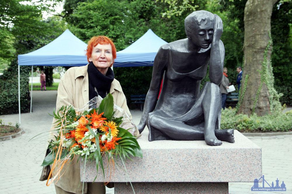 Inge Andler-Laurenzwurde am 2. April 1935 in der Hüttenstadt geboren, das Foto zeigt sie neben der Skulptur ´Weinende Mutter´ in den Kleinschen Anlagen (Foto: Stadt)
