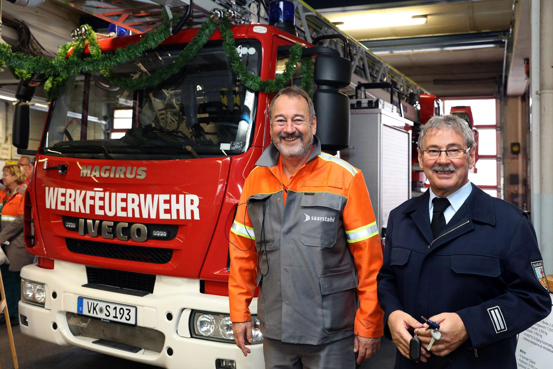 Vor der neuen Drehleiter: Arbeitsdirektor Peter Schweda und der zum Leitenden Werkbrandoberinspektor ernannte Wolfgang Besse (Foto: Saarstahl AG)