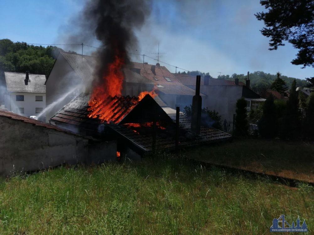Die Feuerwehr wurde zu einem Brand eines Holzgebäudes, welches als Lagerstätte genutzt wird, alarmiert. Bei Ankunft der ersten Kräfte stand das Gebäude bereits in Vollbrand und drohte auf weitere, teils angebaute Gebäude, sich auszubreiten. Es wurde umgehend mit mehreren Trupps unter PA eine Riegelstellung zu den angrenzenden Gebäuden errichtet und von einem weiteren Trupp ein Frontalangriff durchgeführt, so dass diese gehalten werden konnten. Im weiteren Verlauf wurde ein Löschangriff mittels Mittelschaum aufgebaut und der Brand entsprechend abgelöscht. Nach dem Schaumangriff wurde der gesamte Bereich mittels Wärmebildkamera auf noch bestehende Glutnester kontrolliert und diese gezielt abgelöscht. Anschließend wurde die Einsatstelle an die Polizei und den Eigentümer übergeben. (Foto und Beschreibung: Feuerwehr Völklingen)