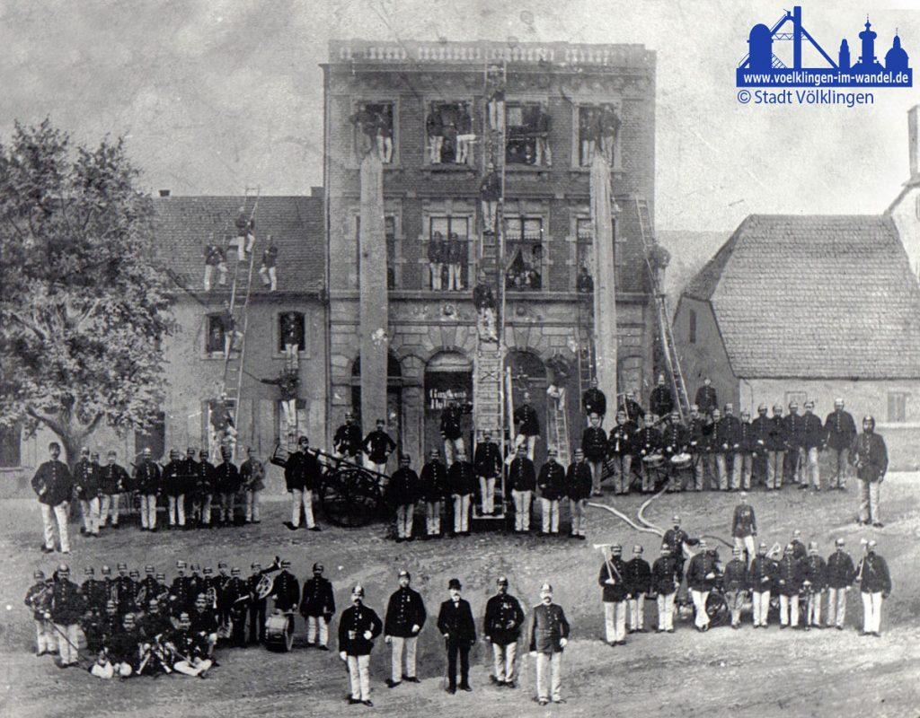 Die Feuerwehr Völklingen bei einer Übung in der damaligen Wilhemstraße 7 im Jahre 1885 (Varietehaus [Variete=Theater] Jakobs Nikolaus) - eine Besonderheit: Diese Fotomontage zeigt als einziges bekannte Bild den damaligen Bürgermeister Carl Stürmer - im Vordergrund in der Mitte.